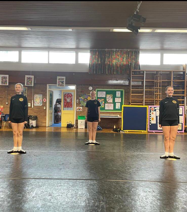 Three Irish dancers practicing turn-out